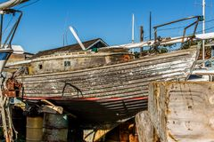 Rustic wooden sailboat in need of a paint job. Sailboat is blocked on the hard in a boatyard in Tomales bay Royalty Free Stock Images