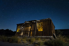 Rustic wooden shack at night in desert. Remains of old wood rustic shack in desert against night skies with stars Royalty Free Stock Images