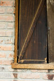 Rustic Wooden Shuttered Window From A Brick Stable Stock Photo