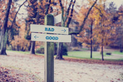 Rustic wooden sign in an autumn park with the words Bad - Good Royalty Free Stock Photo