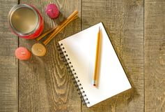 Rustic wooden table with blank white notebook and pencil, coffee Stock Photos