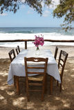 Rustic wooden table and chairs near the beach in Crete Royalty Free Stock Images