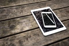 Rustic wooden table with digital tablet and smartphone. View from above Stock Images