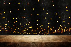 Rustic wooden table in front of glitter black and gold bokeh lights. Rustic wooden table in front of glitter black and gold bokeh lights royalty free stock images