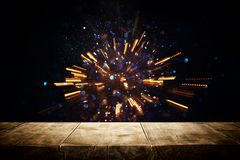 rustic wooden table in front of glitter lights burst. defocused. stock photos
