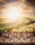 Rustic wooden table over wheat field and sunset sky, nature background. Stock Photo