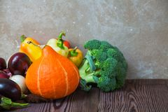 Rustic wooden table pumpkin eggplant broccoli pepper Stock Photography
