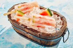 Rustic wooden tub with fresh watermelon popsicles Royalty Free Stock Images
