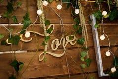 Rustic wooden wedding backgdrop for wedding. Love letters inscription. Decorative lights. stock images