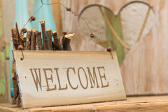 Rustic wooden Welcome sign. Standing on a wooden shelf in front of a wood panel with a cut out heart offering a warm country welcome Stock Images