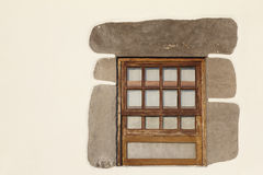 Rustic wooden window with stone frame over a white wall Stock Images