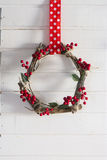 Rustic wooden wreath handmade red barries, hanging on a polka dot ribbon Royalty Free Stock Photography