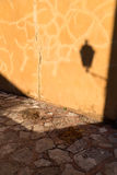Rustic Yellow Plaster Wall and Stone Path with Lantern Shadow Royalty Free Stock Photos
