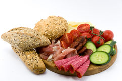 Rustical breakfast on wood plate. Whole grain core bun sausage, ham, salami, cheese, tomato and cucumber  white background Stock Images