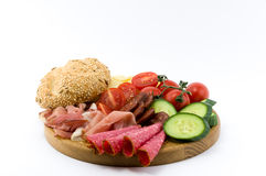 Rustical breakfast on wood plate. Whole grain core bun sausage, ham, salami, cheese, tomato and cucumber  white background Stock Photos