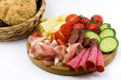 Rustical breakfast on wood plate. Whole grain core bun sausage, ham, salami, cheese, tomato and cucumber  white background Royalty Free Stock Photo