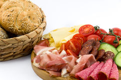 Rustical breakfast on wood plate. Whole grain core bun sausage, ham, salami, cheese, tomato and cucumber  white background Royalty Free Stock Photos