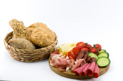 Rustical breakfast on wood plate. Whole grain core bun sausage, ham, salami, cheese, tomato and cucumber  white background Stock Photo