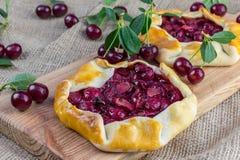 Rustical sura Cherry Pie på jutetyg med några sura körsbär Arkivfoton