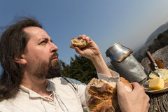 Rustically man with long hair eating bread in the nature Stock Photos