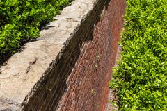 Rusticated stone cap on a red brick retaining wall, abundant greenery. Horizontal aspect royalty free stock photos