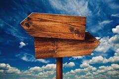 Rustico in bianco di fronte al segno di legno di direzione contro le nuvole Immagine Stock Libera da Diritti