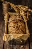 Rustiek brood in bakvorm en tarwe op uitstekende houten lijst royalty-vrije stock afbeelding