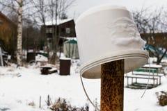 Rustiek de winterlandschap met een oude witte plastic emmer op een ijzer roestige pijler royalty-vrije stock foto