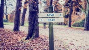Rustiek houten teken met de woordenliefde - Haat Stock Foto