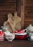 Rustiek keukenstilleven Emailleerde de olijf scherpe raad, kruik bloem, kommen, pan, kruik, juskom Op donker bruin houten Ta Royalty-vrije Stock Afbeelding