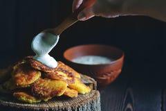 Rustieke aardappelpannekoeken met zure room stock foto