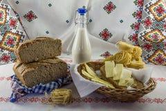 Rustieke achtergrond: artisanaal brood, melkfles, deegwaren en boterhammen en boter in een rieten mand royalty-vrije stock afbeelding