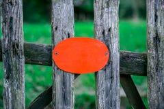 rustieke houten omheining die een lege oranje raad houden stock afbeelding