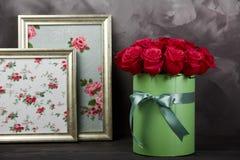 Rustieke huisdecoratie: rood rozenboeket in groene van de giftdoos en foto kaders op donkere grijze rustieke achtergrond Weinig d Royalty-vrije Stock Fotografie