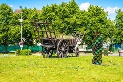 Rustieke Kar Uitstekende houten hooiwagen Monument in een modern dorp royalty-vrije stock afbeeldingen