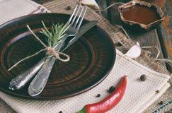 Rustieke lijst die met kleiplaat, bestek, pepermolen, flessen wijn, greens, groenten en kruiden plaatsen De stijl van het land Ex Stock Foto