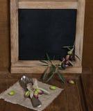 Rustieke lijst die met olijfdecor plaatsen op oude houten lijst Stock Afbeeldingen