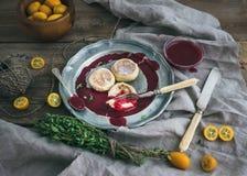 Rustieke ontbijtreeks Russische kaascakes op een uitstekende metaalplaat met lingonberry jam, verse kumquats, thyme, decoratiekab Stock Foto's