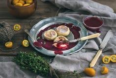 Rustieke ontbijtreeks Russische kaascakes op een uitstekende metaalplaat met lingonberry jam, verse kumquats, thyme, decoratiekab Stock Foto