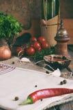 Rustieke samenstelling met pepermolen, tomaat souce, flessen wijn, greens, groenten en kruiden De stijl van het land Het bakken o Royalty-vrije Stock Foto's