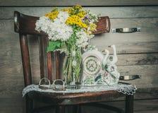 Rustieke Stoel met Bloemen in een Vaas Stock Fotografie