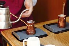 Rustieke Turkse cezve, koffiekan, ibrik met gekookte koffiebonen, water, kruiden, kaneel, zout op elektrisch fornuis en houten li stock foto's