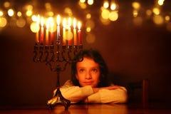 Rustig beeld van de Joodse achtergrond van de vakantiechanoeka met leuk meisje die menorah & x28 bekijken; traditionele candelabr royalty-vrije stock foto's