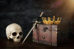 rustig beeld van mooie koningin/koningskroon over oude borst, menselijk schedel en zwaard fantasie middeleeuwse periode royalty-vrije stock foto's