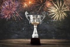 rustig beeld van trofee over houten lijst en donkere achtergrond, met abstract vuurwerk Stock Foto