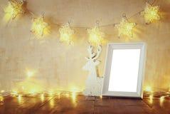 Rustig en wijnoogst gefiltreerd beeld van houten rendier en leeg kader met slinger warme lichten Malplaatje klaar om fotografie t stock afbeelding