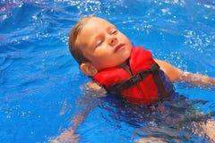 Rustig jong geitje in vest die op haar terug bij de pool drijven royalty-vrije stock afbeelding