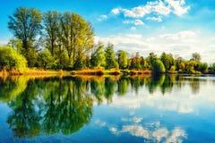 Rustig lakeshorelandschap met blauw hemel en water stock afbeeldingen