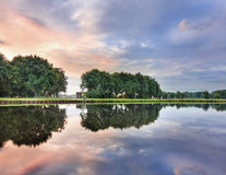 Rustig landschap met een kanaal, bomen, multicolored hemel en dramatische wolken, Tilburg, Nederland royalty-vrije stock foto
