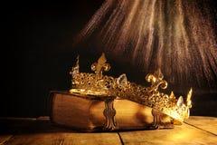 rustig van koningin/koningskroon op oud boek Gefiltreerde wijnoogst fantasie middeleeuwse periode stock foto's
